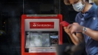 A pedestrian wearing a protective face mask walks past an automated teller machine (ATM) outside a Banco Santander SA bank branch in Madrid, Spain, on Friday, July 24, 2020. Banks in Italy and Spain, among the most exposed to swings in European sovereign bonds, don't plan to make use of capital relief intended to soften the impact of potential losses from such debt. Photographer: Paul Hanna/Bloomberg