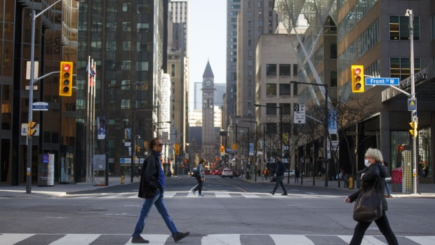 Morning commuters cross Yonge Street at Bay Street in the financial district of Toronto, Ontario, Canada, on Friday, May 22, 2020.