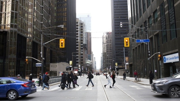 Pedestrians cross a street in the financial district of Toronto, Ontario, Canada, on Friday, Feb. 14, 2020. Canadian stocks declined with global markets, as authorities struggled to keep the coronavirus from spreading more widely outside China. However, investors flocking to safe havens such as gold offset the sell-off in Canada's stock market.