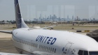 The Manhattan skyline stands past a United Airlines Holdings Inc. airplane on the tarmac at Newark International Airport (EWR) in Newark, New Jersey, U.S., on Tuesday, June 9, 2020. Airline losses are surging to unprecedented levels expected to be more than three times those following the 2008 global economic slump, according to the industry's main trade group.
