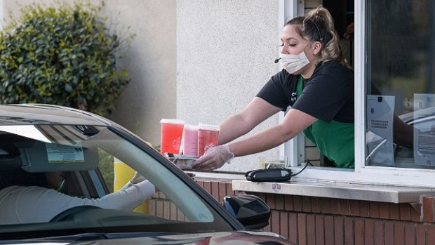 A Starbucks Corp. employee wearing a protective mask and gloves hands a customer an order from a drive-thru window at a store in Hercules, California, U.S., on Tuesday, April 7, 2020.