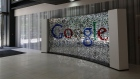 A visitor passes a sign featuring Google Inc.'s logo inside their U.K. headquarters at Six St Pancras Square in London.