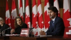 Chrystia Freeland speaks alongside Justin Trudeau at an Ottawa news conference on Oct. 9.
