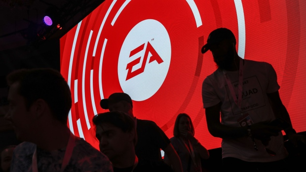 The silhouettes of attendees are seen standing in front of a Electronic Arts Inc. (EA) logo displayed on a screen during the company's EA Play event ahead of the E3 Electronic Entertainment Expo in Los Angeles, California, U.S., on Saturday, June 9, 2018.