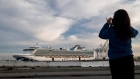 A person takes a photograph of the Carnival Corp. Grand Princess cruise ship docked at the Port of Oakland in Oakland, California, U.S., on Monday, March 9, 2020. The cruise ship that spent days circling the waters off San Francisco with people sickened by the new coronavirus returned to land at an isolated dock, to begin the long process of offloading passengers into quarantine.