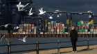 A woman feeds birds against a backdrop of shipping containers on the dockside at the Port of Felixstowe Ltd. in Felixstowe, U.K., on Thursday, Nov. 19, 2020. The organization responsible for setting global environmental standards for shipping approved rules designed to curb the industry's carbon emissions, triggering criticism that its measures won't do enough to help tackle climate change. Photographer: Chris Ratcliffe/Bloomberg