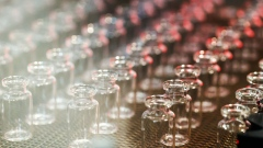 Glass vials move along a production line conveyor at the Gerresheimer AG medical glassware factory in Buende, Germany, on Tuesday, Aug. 11, 2020. Gerresheimer has built up capacity and most of its factories are operating around the clock as the company holds talks with pharma companies, working on a coronavirus vaccine. Photographer: Alex Kraus/Bloomberg