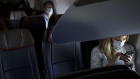 Passengers wear protective masks sit on a Boeing Co. 737-800 during an American Airlines Group Inc. flight departing from Los Angeles International Airport (LAX) Los Angeles, California, U.S., on Saturday, June 13, 2020. The market for jet fuel, along with an increase in flight bookings since early May, is signaling that at least some Americans are ready to take to the skies again after foregoing the pleasures of travel.
