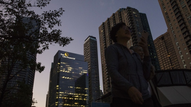 Pedestrians walk past the Sun Life Financial Inc. headquarters, left, in Toronto, Ontario, Canada, on Sunday, Aug. 11, 2019. Sun Life reached its lowest ever coupon for any of its bonds with the issuance of its first sustainable notes in a fresh sign that demand for such debt is increasingly driven by general investors scratching for some yield above inflation.
