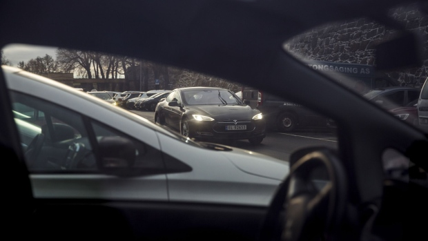 A Tesla Motors Inc. Model S electric vehicle (EV) drives in Oslo, Norway, on Monday, Nov. 21, 2016. The International Energy Agency forecasts that global gasoline consumption has all but peaked as more efficient cars and the advent of electric vehicles from new players such as Tesla Motors Inc. halt demand growth in the next 25 years. Photographer: Fredrik Bjerknes/Bloomberg