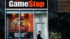 A pedestrian wearing a protective mask walks past a a GameStop Corp. store in the Herald Square area of New York, U.S., on Friday, Nov. 27, 2020. With sparse crowds and none of the stampedes of holidays past, some retail watchers started to refer to Black Friday as Blase Friday instead -- and that was even before the virus hit.
