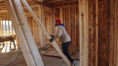 A contractor moves wooden beams to frame interior walls while working at a home under construction at The Estates at Kelley Farms new housing development in Ballston Lake, New York, U.S., on Friday, Dec. 11, 2020. The U.S. Census Bureau is scheduled to release housing starts figures on December 17.