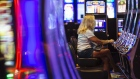A visitor wears a protective mask while playing a slot machine at the Ocean Casino Resort in Atlantic City, New Jersey, U.S., on Thursday, July 2, 2020. Atlantic City gambling, dealt a blow by newly opened betting markets in other states, was enjoying a slow comeback when Murphy ordered all nine casinos closed on March 16. Photographer: Angus Mordant/Bloomberg