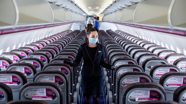 A member of flight crew sits next to social distancing signs at London's Heathrow Airport. Photographer: Chris Ratcliffe/Bloomberg