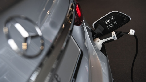 An electric charging plug refuels a Mercedes-Benz E-Class electric automobile. Photographer: Andreas Gebert/Bloomberg