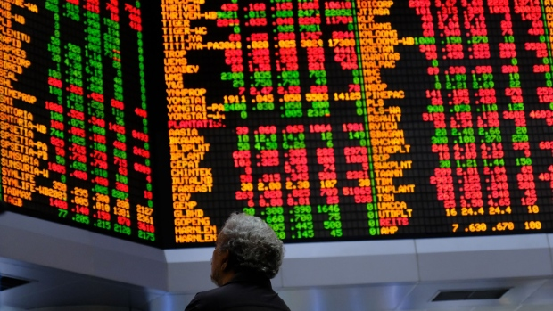 A person looks at stock prices displayed in the trading gallery of the RHB Investment Bank Bhd. headquarters in Kuala Lumpur, Malaysia, on Tuesday, Feb. 17, 2020.