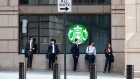 People wearing protective masks wait in line outside a Starbucks on Wall Street near the New York Stock Exchange on Nov. 9.