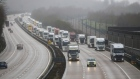 A police car escorts trucks on the M20 motorway in Operation Stack near Ashford, U.K., on Monday, Dec. 21, 2020. Britain's biggest port stopped all traffic heading to Europe, triggering delays to food supplies after the discovery of a new variant of the virus prompted a wave of countries to ban travel from the U.K. Photographer: Chris Ratcliffe/Bloomberg