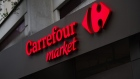 A logo outside a Carrefour Market supermarket, operated by Carrefour SA, in Paris, France, on Wednesday, Jan. 13, 2021. Alimentation Couche-Tard Inc., the Canadian convenience-store operator that owns the Circle K chain, is exploring a takeover of French grocer Carrefour SA, a deal that would create a trans-Atlantic retail giant. Photographer: Nathan Laine/Bloomberg