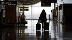 A passenger wheels a suitcase through a deserted arrivals hall at Madrid Barajas airport, in Madrid. Photographer: Paul Hanna/Bloomberg