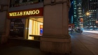 Pedestrians pass in front of a Wells Fargo & Co. bank branch at night in New York.