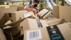 An employee wearing a protective mask scans a package at an Amazon.com Inc. fulfillment center in Kegworth, U.K., on Monday, Oct. 12, 2020. Prime Day, a two-day shopping event Amazon unveiled in 2015 to boost sales during the summer lull, usually occurs in July, but this year got pushed to Oct. 13 in 19 countries, including Brazil, with over 1 million products for sale worldwide. Photographer: Chris Ratcliffe/Bloomberg