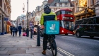 A takeaway food courier, working for Deliveroo, operated by Roofoods Ltd., cycles in the Soho district of London, U.K., on Tuesday, Sept. 29, 2020. Covid-19 lockdown enabled online and app-based grocery delivery service providers to make inroads with customers they had previously struggled to recruit, according the Consumer Radar report by BloombergNEF. Photographer: Hollie Adams/Bloomberg