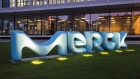 The Merck KGaA logo stands illuminated at dusk outside the pharmaceutical company's headquarters in Darmstadt.