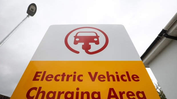 A sign for an electric vehicle charging area stands at a Royal Dutch Shell Plc petrol filling station in Ewell, U.K., on Wednesday, Sept. 30, 2020. Royal Dutch Shell Plc will cut as many as 9,000 jobs as Covid-19 accelerates a company-wide restructuring into low-carbon energy.