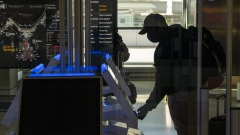 A traveler wearing a protective mask uses an automated kiosk to check-in at the Delta Air Lines Inc. check-in area at San Francisco International Airport (SFO) in San Francisco, California, U.S., on Monday, Dec. 21, 2020. Airline passenger numbers in the U.S. totaled 1.06 million on Dec. 20, compared with 2.52 million the same weekday a year earlier, according to the Transportation Security Administration.