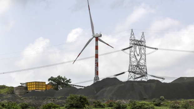 A wind turbine manufactured by Suzlon Energy Ltd. operates beyond an electricity pylon and coal pile at the Ostro Energy Pvt. Dewas Wind Project in Dewas, Madhya Pradesh, India, on Monday, Aug. 14, 2017. As of June, India had 32 gigawatts of wind capacity. The nation is aiming to raise that to 60 gigawatts by 2022 as part of the country's climate pledge. Photographer: Dhiraj Singh/Bloomberg