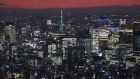 Tokyo Tower, middle, and buildings are lit up in Tokyo, Japan, on Friday, Dec. 25, 2020. Japan's infrastructure is already one of the world's safest and investment in mitigating natural disasters is ramping up. Photographer: Toru Hanai/Bloomberg