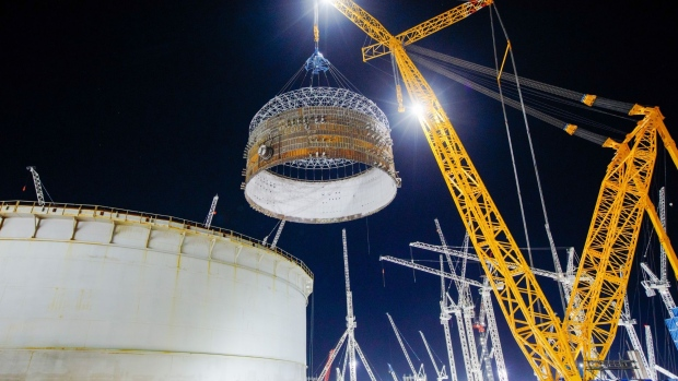 "A crane lifts a prefabricated steel containment ring into position at the nuclear Reactor Unit 1, at Hinkley Point C nuclear power station construction site, near Bridgwater, U.K., on Thursday, Dec. 17, 2020. The world's largest crane, affectionately known as ""Big Carl,"" hoisted the first of three massive steel rings that will encase one of the reactors at Electricite de France SA's nuclear construction site in the U.K., a key milestone in getting the project completed on time."