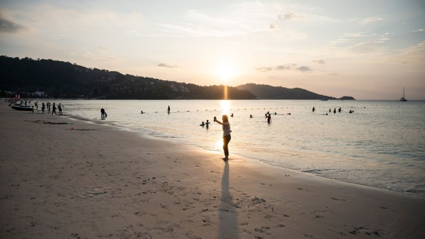 PHUKET, THAILAND - JANUARY 17: A small group of people gather at a relatively empty Patong Beach on January 17, 2021 in Phuket, Thailand. Thailand's tourism-dependent economy was already on life-support before a resurgence of Covid-19 infections, with GDP expected to contract by six per cent in 2020, millions unemployed and record household debt continuing to soar. A fresh lockdown to combat the virus has thrown broad parts of the economy into an extended decline. (Photo by Sirachai Arunrugstichai/Getty Images) Photographer: Sirachai Arunrugstichai/Getty Images AsiaPac