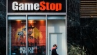 A pedestrian wearing a protective mask walks past a a GameStop Corp. store in the Herald Square area of New York, U.S., on Friday, Nov. 27, 2020.
