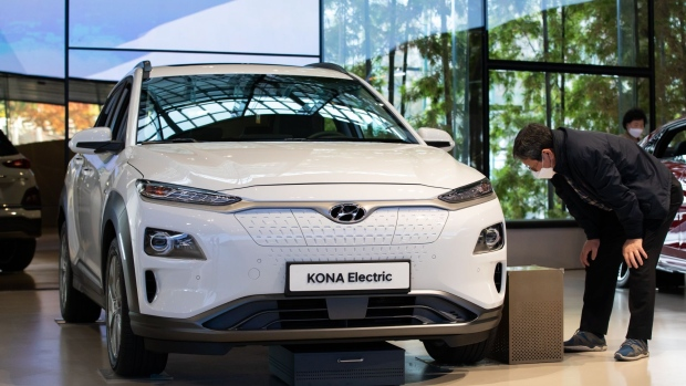 A customer wearing a protective mask looks at a Hyundai Motor Co. Kona electric sport utility vehicle (SUV) on display at the company's Motorstudio showroom in Goyang, South Korea, on Thursday, Oct. 22, 2020.