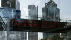 A pedestrian walks along an elevated walkway and an electronic ticker displaying stock figures are reflected in a pane of glass in Pudong's Lujiazui Financial District in Shanghai, China, on Thursday, Feb. 18, 2021. China's stock benchmark erased gains after briefly surpassing its 2007 closing peak, as mainland financial markets opened for the first time following the Lunar New Year break. Photographer: Qilai Shen/Bloomberg