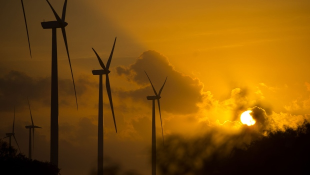 Wind turbines stand during sunset at the Avangrid Renewables' Baffin Wind Power Project in Sarita, Texas, U.S., on Wednesday, June 14, 2017. In the cut-throat Texas energy market, the construction of coastal wind turbines—some 900 in all—has had a profound impact. It's been terrific for consumers, helping further drive down electricity bills, but horrible for natural gas-fired generators.