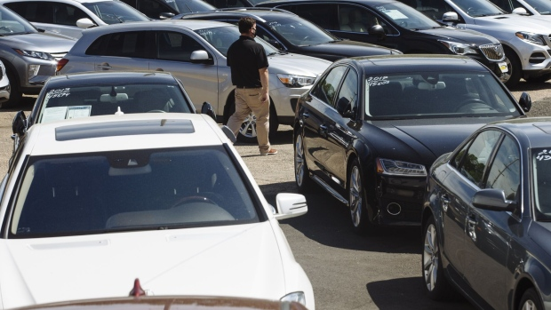 A car dealer walks past cars for sale at a used car dealership in Jersey City, New Jersey, U.S, on Wednesday, May 20, 2020.