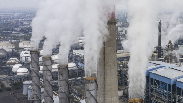 """Exhaust rises from smoke stacks at the Sinopec Zhenhai Refining & Chemical Co. processing facility in this aerial photograph taken on the outskirts of Ningbo, Zhejiang Province, China, on Wednesday, April 22, 2020. China's top leaders softened their tone on the importance of reaching specific growth targets this year during the latest Politburo meeting on April 17, saying the nation is facing """"unprecedented"""" economic difficulty and signaling that more stimulus was in the works. Photographer: Qilai Shen/Bloomberg"""