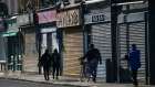 Pedestrians walk past shuttered shops in the Tower Hamlets district of London, U.K., on Monday, March 22, 2021. Skepticism and misinformation are hampering efforts to protect the U.K.'s most diverse and deprived communities.