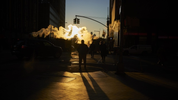 Steam rises as pedestrians cross a street near the New York Stock Exchange (NYSE) in New York, U.S., on Thursday, Dec. 27, 2018. Volatility returned to U.S. markets, with stocks tumbling back toward a bear market after the biggest rally in nearly a decade evaporates. Photographer: John Taggart/Bloomberg