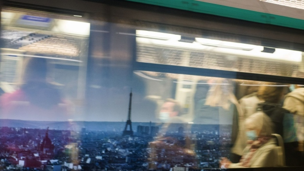 Morning rush hour commuters wear protective face masks while passing a poster showing the Eiffel Tower and city skyline at Champs-Elysees–Clemenceau metro station in Paris, France, on Wednesday, Oct. 14, 2020. After putting six cities including Paris on maximum alert, President Macron Macron may announce additional restrictions on French national television today. Photographer: Nathan Laine/Bloomberg