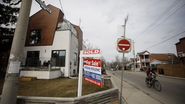 "A ""Sold"" sign on a front lawn of a home in the York neighborhood of Toronto, Ontario, Canada, on Thursday, March 11, 2021. The buying, selling and building of homes in Canada takes up a larger share of the economy than it does in any other developed country in the world, according to the Bank of International Settlements, and also soaks up a larger share of investment capital than in any of Canada's peers. Photographer: Cole Burston/Bloomberg"