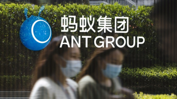 Employees are reflected on a glass panel while walking past a logo at the Ant Group Co. headquarters in Hangzhou, China, on Wednesday, March 24, 2021. China's government has proposed establishing a joint venture with local technology giants that would oversee the lucrative data they collect from hundreds of millions of consumers, according to people familiar with the matter. Photographer: Qilai Shen/Bloomberg