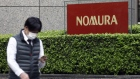 "A pedestrian wearing a protective face mask walks past the Nomura Holdings Inc. signage outside its headquarters in Tokyo, Japan, on Monday, March 29, 2021. Nomura's warning of a ""significant"" potential loss from an unnamed U.S. client is related to the unwinding of trades by Bill Hwangs Archegos Capital Management, according to people familiar with the matter. Photographer: Kiyoshi Ota/Bloomberg"
