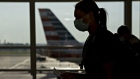 A traveler wearing a protective mask walks past an American Airlines Group Inc. plane tail fin at Ronald Reagan National Airport (DCA) in Arlington, Virginia, U.S., on Tuesday, June 9, 2020.