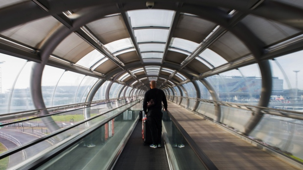A solitary traveler on a moving walkway towards Terminal 4 at Orly Airport, operated by Aeroports de Paris.