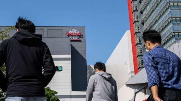 People walk past the Taiwan Semiconductor Manufacturing Co. headquarters in Hsinchu, Taiwan, on Wednesday, April 7, 2021. The TSMC is a key supplier to Apple, and it's the iPhone maker's commitment to become carbon neutral by 2030 that is driving much of the change throughout the supply chain.