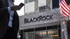 A pedestrian holding a smartphone passes in front of BlackRock Inc. headquarters in New York, U.S, on Tuesday, April 13, 2021. BlackRock Inc. is scheduled to release earnings figures on April 15.